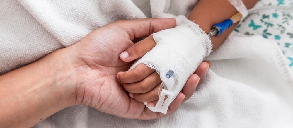 This image shows a mother holding the hand of their child after surgery.