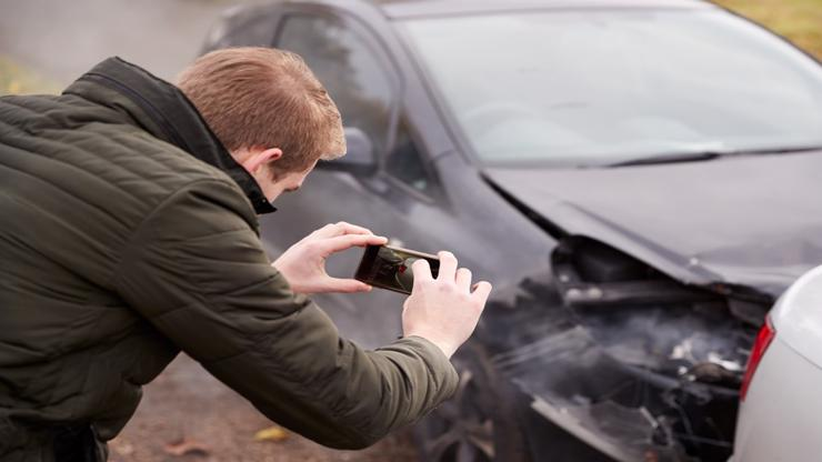 Un hombre tomando fotos de un automóvil después de un accidente en Augusta