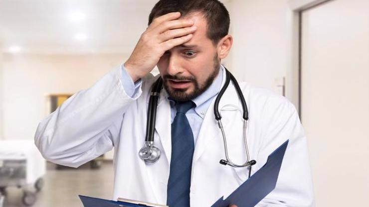 A doctor reading a notebook realizing he has made a mistake.