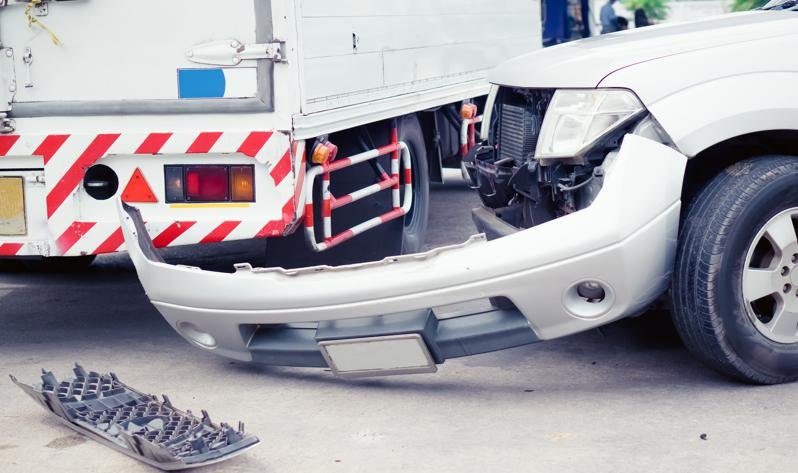 The aftermath of a commercial truck accident with a car.