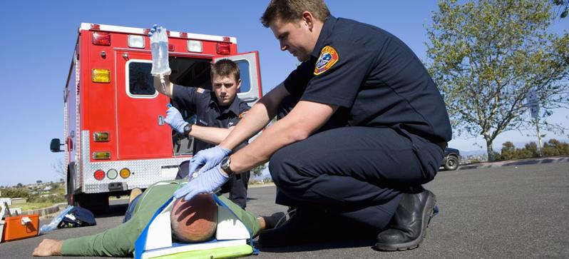 This image shows a seriously injured man on a stretcher with paramedics.
