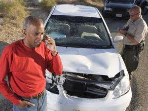 A man on his phone talking to lawyer while a police officer documents damages after a car accident in Charlotte, NC