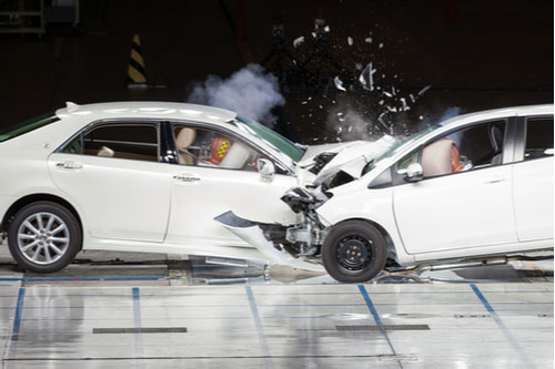 Front-end collision during crash test with front of two cars torn open