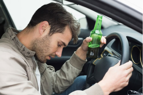 Man drinking beer while driving his car
