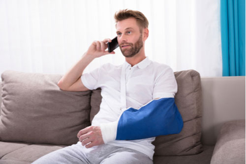Man with arm in cast and sling calling Charlotte rear-end car accident lawyer on mobile phone