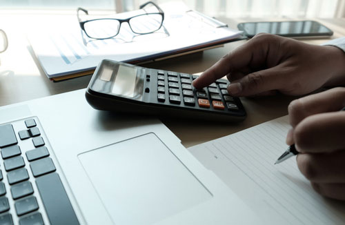 Closeup of Charlotte rollover accident lawyer computing financial damage amount on calculator