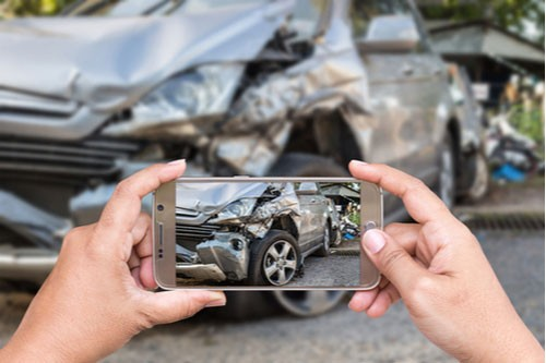 Close up of woman's hands holding smartphone and taking photo of car accident