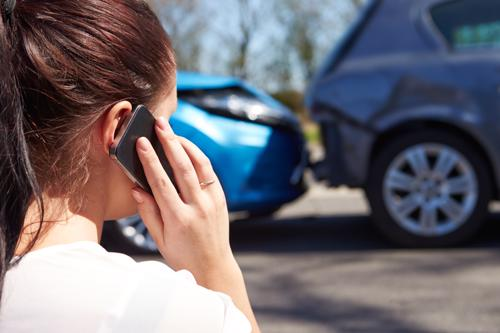 A woman calling her insurance after a rear-end car accident.